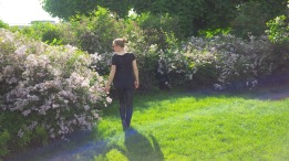 Photo ofMaja Monrue, the author of Awakening Her, standing in a garden.